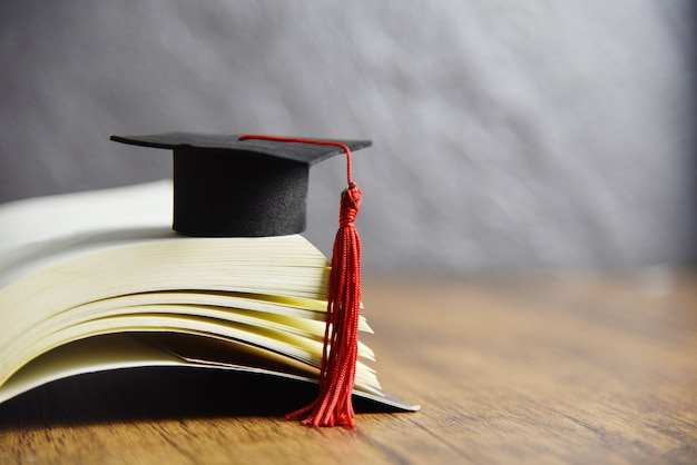 Graduation cap on a book on the wooden table Premium Photo