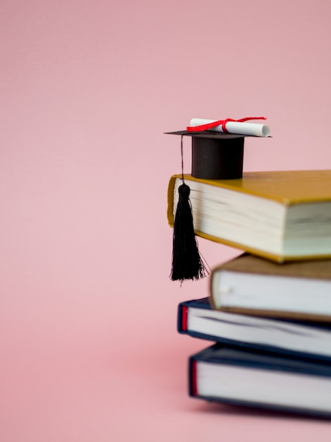 Graduation cap and diploma on different books with copy space Premium Photo