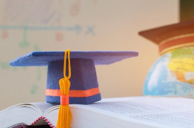 アメリカ地球世界世界モデルマップのぼかしで教科書を開く際の卒業帽 Premium写真