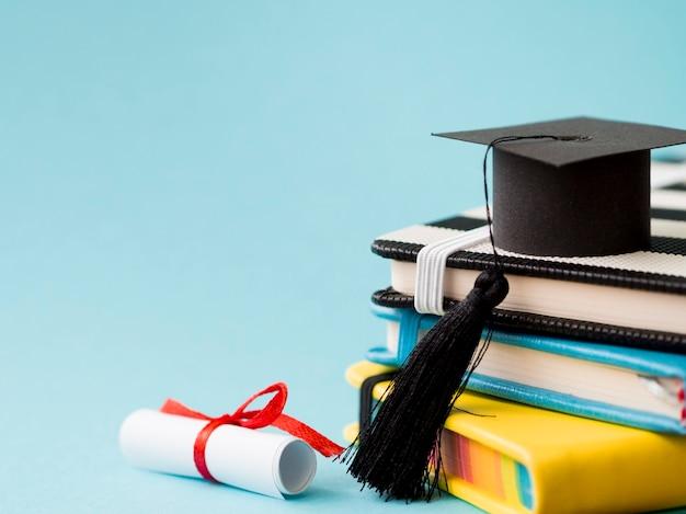 コピースペースで本の山に卒業の帽子 Premium写真