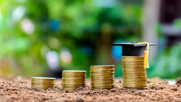 Graduation cap on a stack of coins, nature green blur concept education saving money Premium Photo