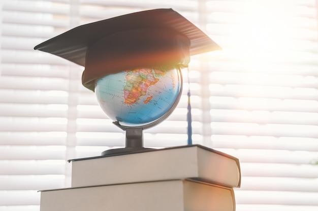 Graduation cap on top of the globe Premium Photo