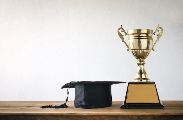 木製テーブルの上のチャンピオンゴールデントロフィーと卒業の帽子 Premium写真