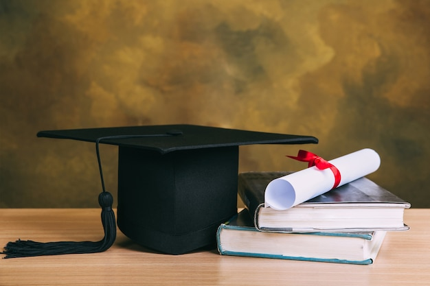 Graduation concept.graduation cap, books with degree paper on wood table Premium Photo