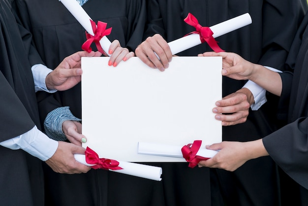 Graduation concept with students holding blank certificate template Free Photo
