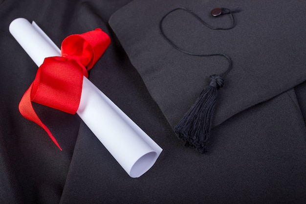 Graduation day. a gown, graduation cap, and diploma and laid out ready for graduation day Premium Photo