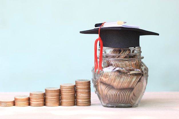 Graduation hat on coins money in the glass bottle on white background Premium Photo