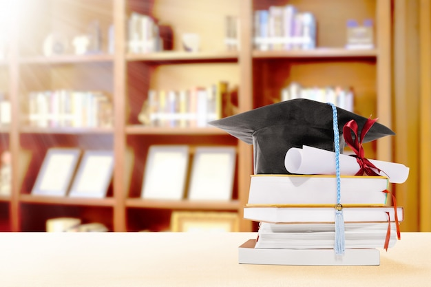 Graduation hat, diploma scroll and books on the table with bookshelf Premium Photo