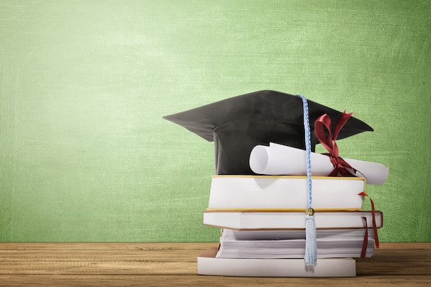 Graduation hat, diploma scroll and books on the wooden table Premium Photo