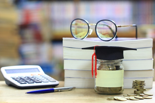 Graduation hat on the glass bottle on bookshelf in the library room, saving money for education concept Premium Photo