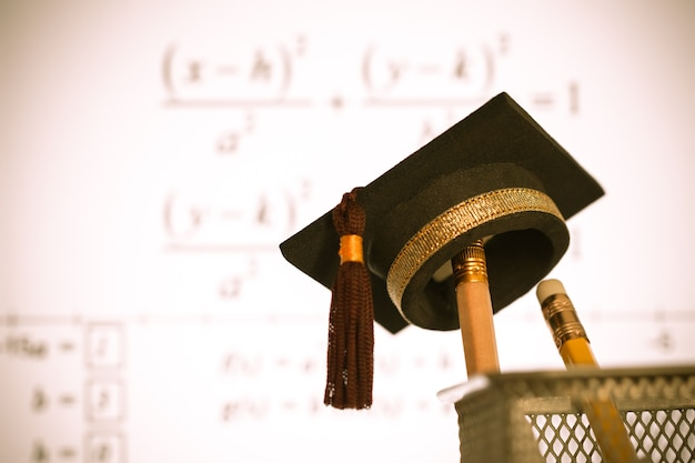 Graduation hat on pencils with formula equation graph on projector screen at university Premium Photo