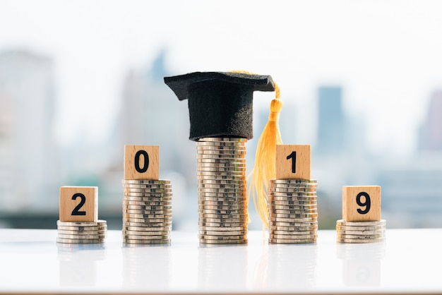 Graduation hat on top coin stack with 2019 wooden blocks. Premium Photo