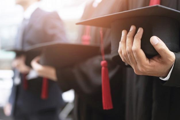 卒業、学生は大学の最初の成功の卒業生の間に帽子を手に持っています Premium写真