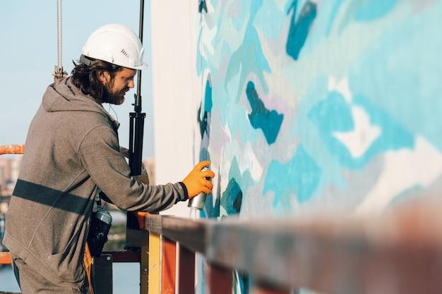 Граффити-художник рисует белую стену на большой высоте в волнах. Premium Фотографии