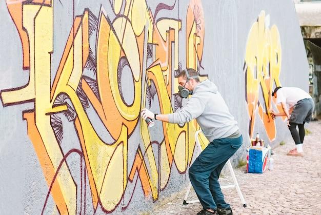 회색 벽에 화려한 벽화를 그리는 낙서 예술가 프리미엄 사진