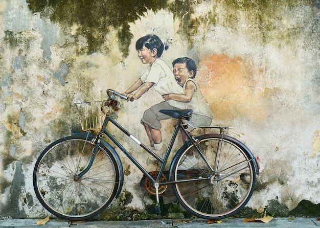 Graffiti of a children on a bicycle Free Photo