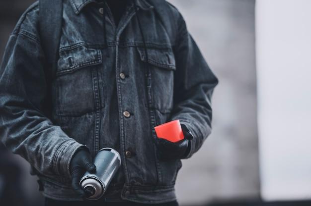 Граффити в джинсовом пальто с баллончиком с краской. подготовка к работе Premium Фотографии