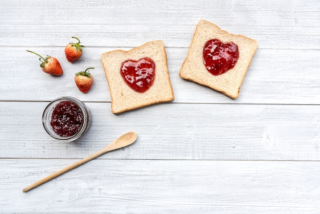 Grain bread topping with red heart shaped homemade strawberry jam and strawberries fruits Premium Photo