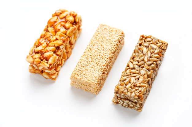 Grain granola bar with peanuts, sesame and seeds in a row. top view three assorted bars, isolate Premium Photo