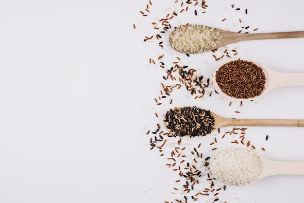 Grains spilled around spoons with rice Free Photo
