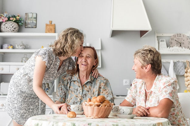 Grand daughter kissing her smiling granny during breakfast Free Photo