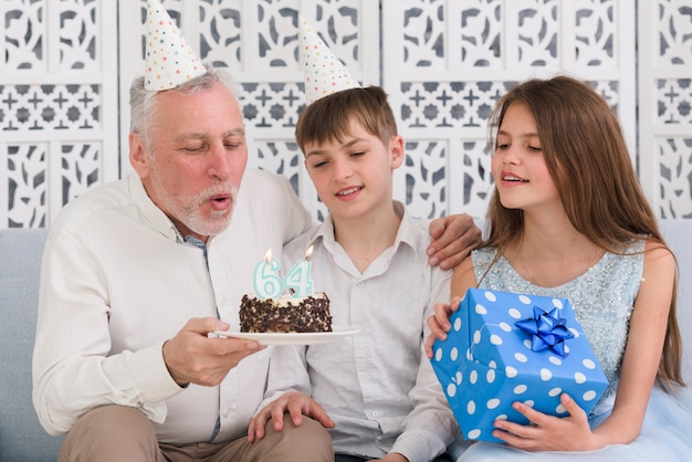 Grandfather blowing birthday candle with his grandchildren Free Photo