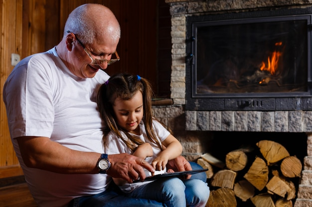Grandfather and granddaughter using tablet of a house near the fireplace Premium Photo