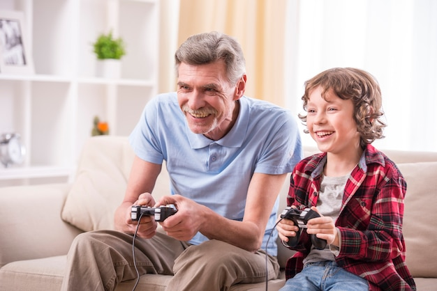 Grandfather and grandson are playing video games at home. Premium Photo