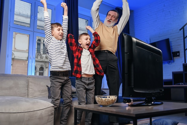 Grandfather and grandson watching television. grandfather and grandson enjoying at home. Premium Photo