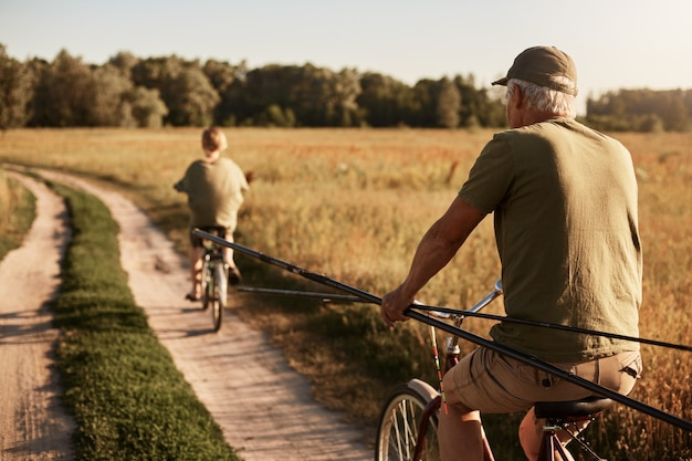 Grandfather and his grandson go fishing on bicycles, back view of family in meadow on bikes with fishing rods, senior man and young guy wearing casual closing, beautiful field and trees. Free Photo
