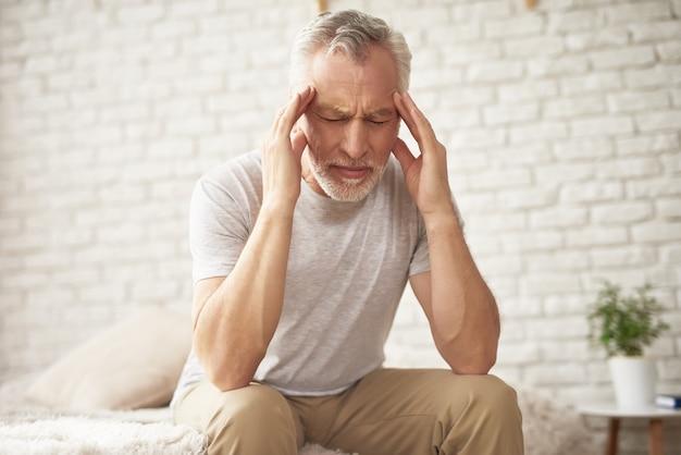 Grandfather holding head blood pressure headache. Premium Photo