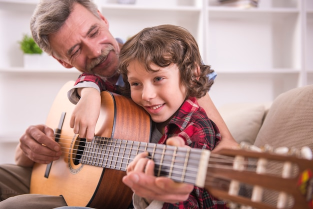 Grandfather is playing guitar with his grandson  Photo