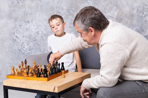 Grandfather playing old chess with grandson. the boy and his grandpa are sitting on the sofa in the living room and playing. senior man teaches a child to play chess Premium Photo