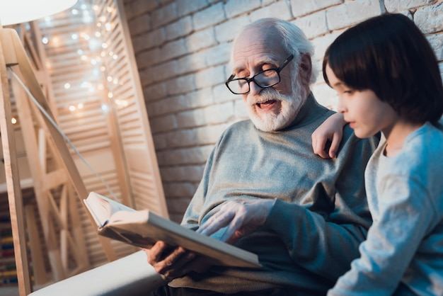 Grandfather reading fairy tale to little grandson Premium Photo