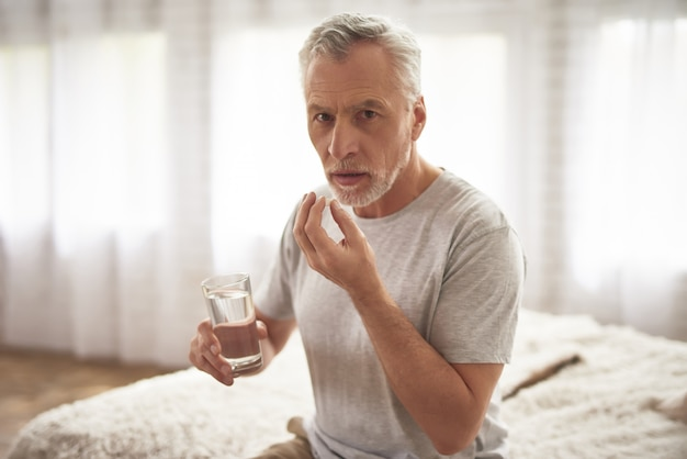 Grandfather taking pills in morning chronic pain. Premium Photo