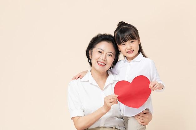 Бабушка и внучка держат любовь Premium Фотографии