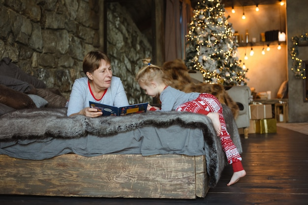 Grandma and granddaughter in christmas pajamas reading a book, lying on the bed in the chalet. family christmas concept. Premium Photo