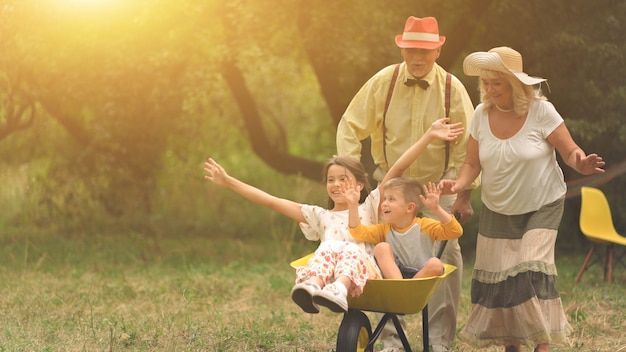 Grandma and grandpa are pushing their grandchildren in a wheelbarrow Premium Photo