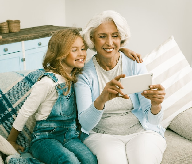 Grandma and her cheerful granddaughter making selfie Premium Photo