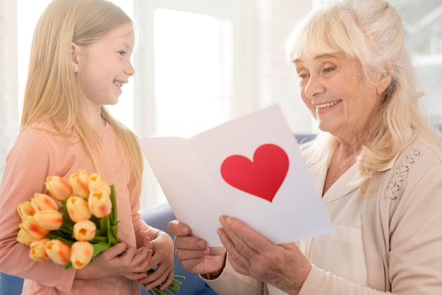 Grandma with flowers and greeting card from girl Free Photo