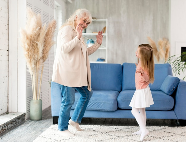 Grandma with girl at home playing Free Photo