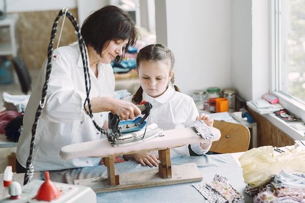 工場で小さな孫娘の鉄の服を着たおばあちゃん 無料写真