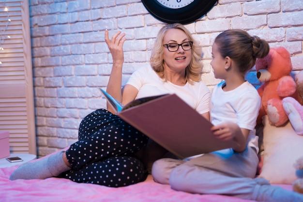 Бабушка и внучка читают дома. Premium Фотографии