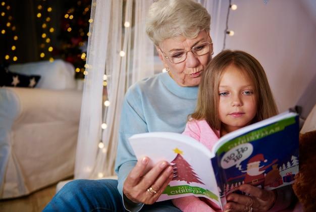 Бабушка и внучка, читая сборник рассказов в постели Бесплатные Фотографии