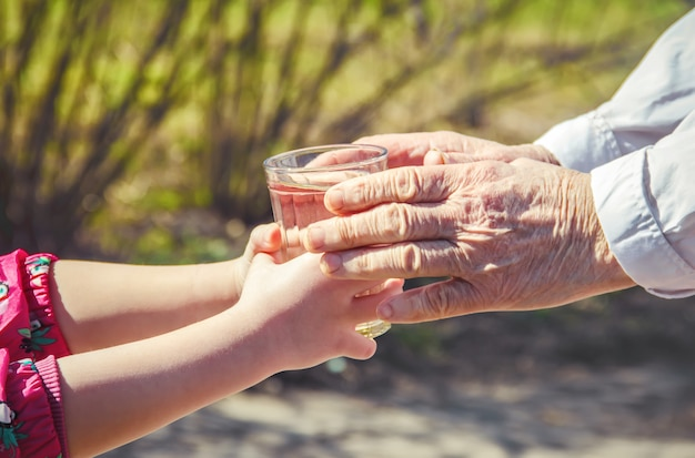 Grandmother giving a glass of clean water to a child. selective focus. Premium Photo