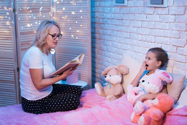 Grandmother and granddaughter are reading children's book at night at home Premium Photo