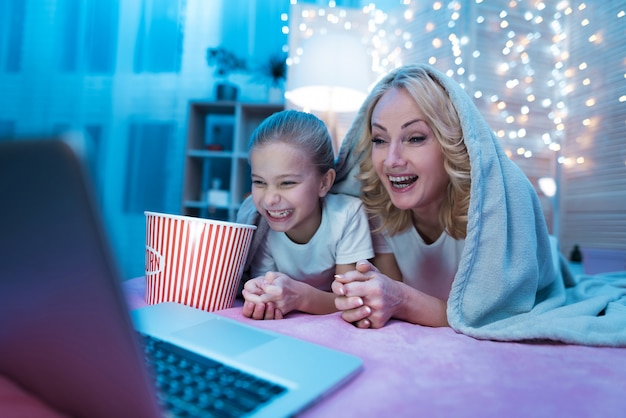 Grandmother and granddaughter are watching movie on laptop. Premium Photo