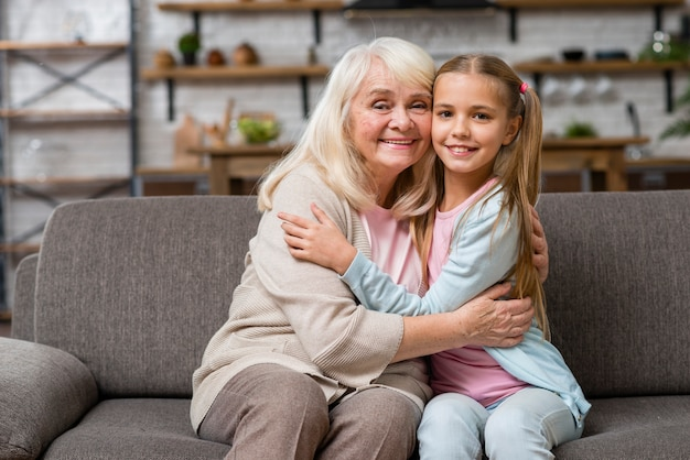 Grandmother and granddaughter hugging front view Free Photo