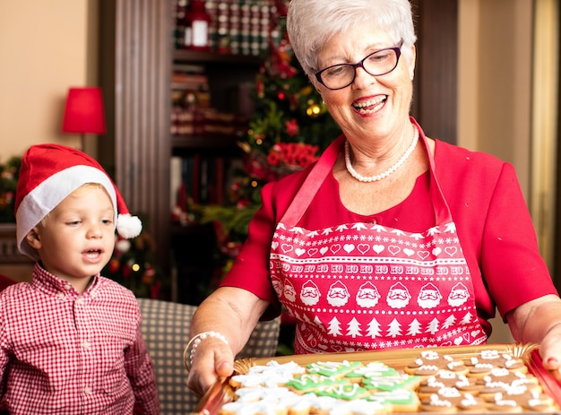 Grandmother holding a tray with christmas cookies Free Photo