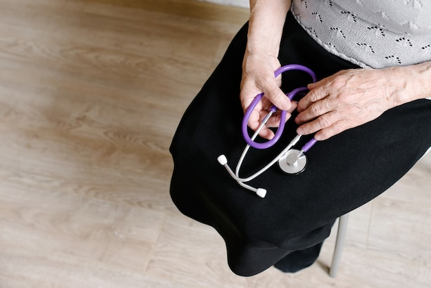 The grandmother holds a stethoscope in hand Premium Photo